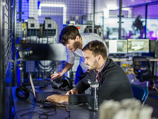 Two men leaning over a computer surrounded by VR and robotics equipment