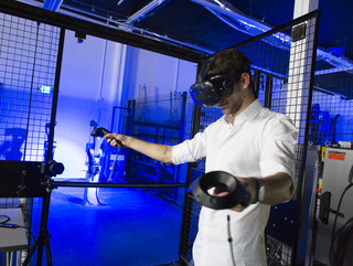 A staff member with a VR headset operating robots at the IDEAS campus