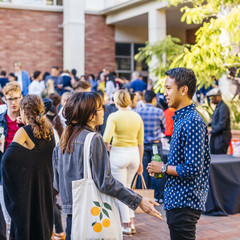 A group of students and alumni gathered in Perloff Hall courtyard