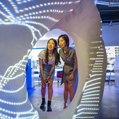 Two female students looking through an interactive exhibition