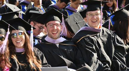 Image of three smiling students in graduation regalia