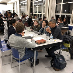 Image of students gather around a table with a professional sharing feedback on their portfolios