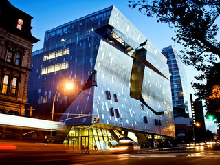 Exterior shot of the Cooper Union Building at 41 Cooper Square in New York. The façade is made up of a stainless steel curtain wall that wraps the entire building.