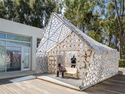 Photo of the exterior of BI(h)OME, a speculative Accessory Dwelling Unit framed with two-by-fours and bent metal poles and wrapped in translucent plastic sheeting.