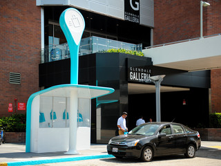 Image of a Curbside Pickup Pod outside Glendale Galleria, a blue-and-white fiberglass kiosk that allows you to shop via an app and conveniently pickup orders from retailers.