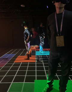Image of people using a VR experience standing on a grid
