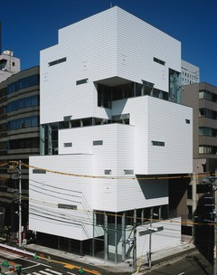 Image of a white angular building on the corner of a street in Sendai, Japan.