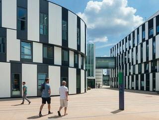 Image of students walking through Campus Wu, a cluster of curved black and white panelled buildings.