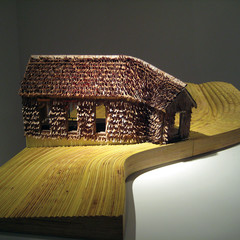 Image of Raspberry Fields, a model of a house on a yellow wooden base with brown curled cedar shingles.