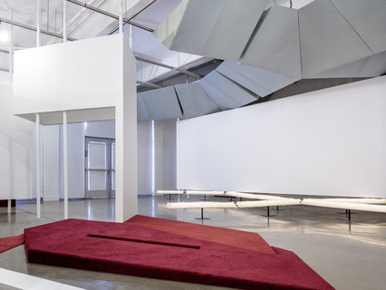 Image of an exhibition featuring red carpet and metal duct-like sculpture hanging from the ceiling