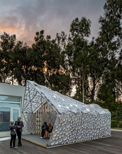 Image of BI(h)OME, a lightweight Accessory Dwelling Unit framed with two-by-fours and bent metal poles and wrapped in translucent plastic sheeting.