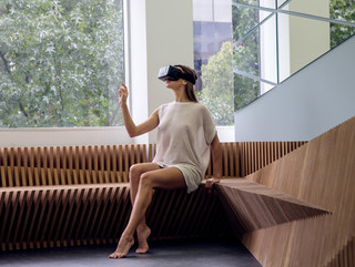 Image of a woman wearing a VR headset sitting on a wooden bench