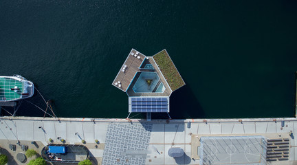 Drone aerial shot of the Urban Rigger, a student housing solution made of shipping containers floating on water.