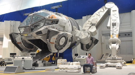 Image of a man sitting in front of a spaceship