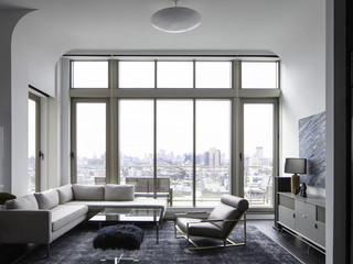 Image of a living room in a penthouse with curved ceilings looking out over the NYC skyline