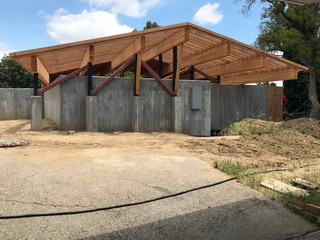 Image of a house under construction with a wood roof and concrete walls