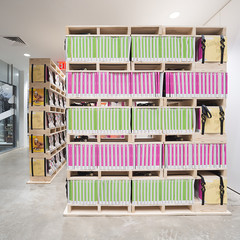 Image of a colorful bookshelf inside a room with concrete floors
