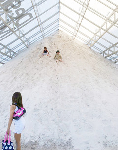 Image of two children sliding down a sand bank inside a structure