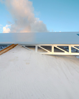 Image of a sand pile rising up to almost cover a structure