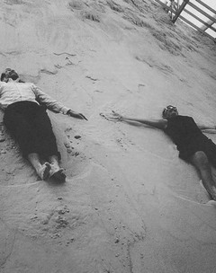Image of two people lying on a sand bank