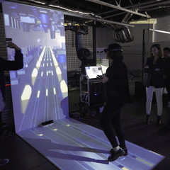 Image of a woman experiencing a VR environment surrounded by a group of people