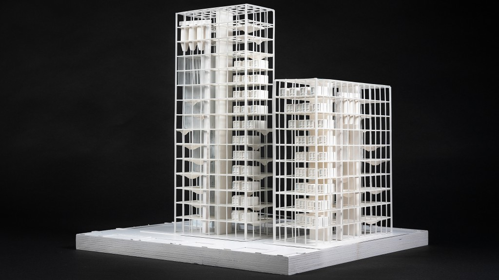 Model of a white high rise building against a black background