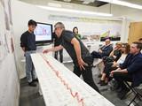 Jurors gather around a model of Green New Wave by Haoyu Chen, Liyao Chen, Kenny Wong, Siqi Zhang