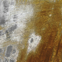 Aerial photograph of dried lake bed with predominantly blue and white coloration on the left and rust on the right.