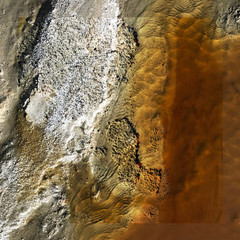 Aerial photograph of dried lake bed with white and tan coloration on the left side that fades to brown in the middle and rusty clouded tones on the right.