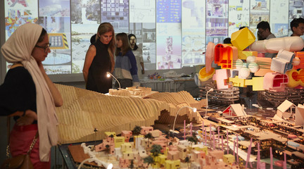 Image of two women looking at the mega-model of structures on the reimagined island of Tuvalu as part of RUMBLE, the end-of-year student exhibition.