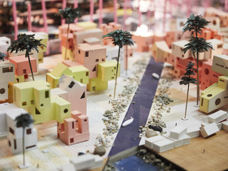 Image of a final student model representing the reimagined island of Tuvalu, with small house, palm trees and a waterway running through.
