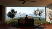 Video still showing a person sitting on a couch in front of a landscape